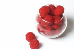 Large red berries are similar to raspberries in a glass vase. Stock Photography