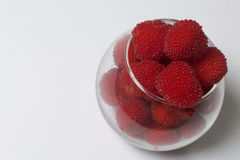 Large red berries are similar to raspberries in a glass vase. Stock Image