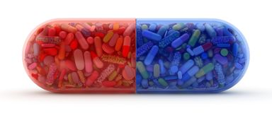 Large red and blue pill filled with colorful pills stock photography