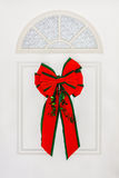 Large Red Bow Hanging on White Door. Huge bright red Christmas bow with green edging made of  velvet ribbon stands out on this white colonial style door.  Small Royalty Free Stock Photo