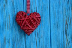 Red braided heart hanging on a blue wooden wall Royalty Free Stock Photography