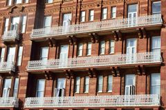 Large red bricked hotel with white balcony Stock Photos