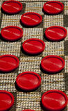 Large red checkers on a cloth board. Royalty Free Stock Images