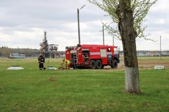 A large red fire rescue vehicle, a truck to extinguish a fire and male firefighters at a chemical, oil refinery against the backgr stock image