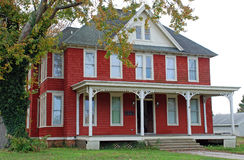 Large Red Folk Victorian 18. Large red home with an ornate porch. Early 1900s American architecture Stock Photos