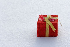 The large red and gold gift in the snow Royalty Free Stock Image