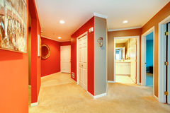 Large red hallway in city apartment with open bathroom door and beige carpet. Stock Photos
