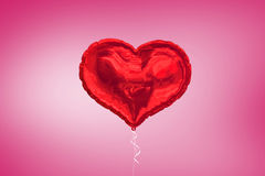 A large red heart balloon on pink background Royalty Free Stock Photo