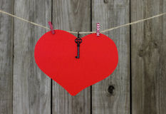 Large red heart sign with key hanging on clothesline by old weathered wood fence Royalty Free Stock Photography