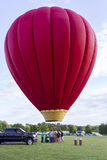 A Large Red Hot Air Balloon Just Above The Ground. A large bright red hot-air balloon hovering over the ground while people help to prepare it to lift off. Photo Stock Photos
