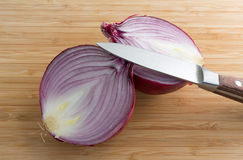 Large red onion halved on cutting board with knife Royalty Free Stock Photography