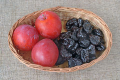 Large red plums  and prunes in in a wicker basket Royalty Free Stock Images