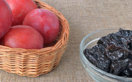 Large red plums in a wicker basket and prunes in a glass cup on Stock Photography