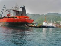 Great red seagoing ship. A large red sea ship, a tanker, stands in the docks. Great tanker in tugboat support Royalty Free Stock Photo