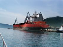 Great red seagoing ship. A large red sea ship, a tanker, stands in the docks. Great tanker in tugboat support Stock Images