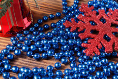 Large red snowflake, red bell and blue beads on wood background Stock Photos