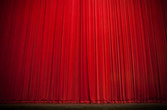 Large Red Stage Curtain. Old style large red performance curtain draped over well worn theatrical stage stock photo