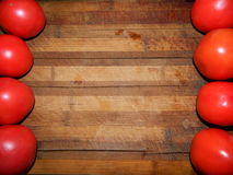 Large red tomatoes bright vegetables on both sides of the wide brown cutting board Stock Photos