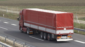 Large Red Truck on Highway. A large commercial trailer truck moves away, traveling down a major highway Royalty Free Stock Images