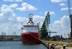 A large red and white sea cargo ship in a port. A large red and white sea cargo ship while parking in the port, front view. There also are some port cranes and stock photos