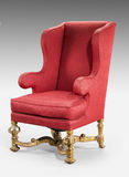 Large red wing chair upholstered in red old antique in need of r Stock Photo