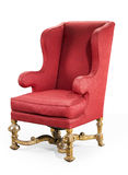 Large red wing chair upholstered in red old antique in need of r Stock Images