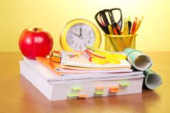 Large reference book and school supplies. The book, a roll of exercise books, a support with handles, an alarm clock and red apple on a yellow background Stock Photography