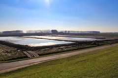 A large reservoir in the polder behind the seawall in zeeland, holland in winter. A large reservoir with mud and water in the dutch countryside behind the stock image