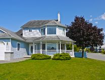 Large residential house with surrounding porch and big green lawn at the entrance. Big family home with black cherry tree beside on blue sky background royalty free stock photos