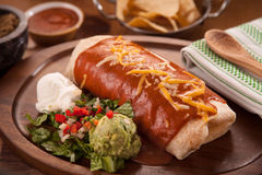 Large restaurant style burrito mexican food dinner with sides of guacamole chips Royalty Free Stock Photo
