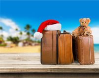 Retro large suitcases and santa hat on beach. Large retro suitcases new year santa hat travel concept object Stock Photos