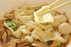 Large rice noodle with braised pork in soup picking by chopstick Royalty Free Stock Image