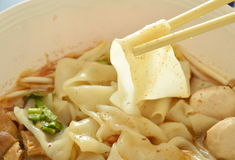 Large rice noodle with braised pork in soup picking by chopstick Royalty Free Stock Photography