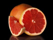 A large ripe grapefruit with cut slices Stock Photos