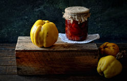 Large ripe quince on a wooden box, a jar of jam on a dark background, rustic style Stock Photo