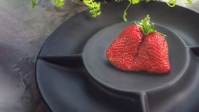 Large ripe strawberries original unusual shape lies on a beautiful black matte plate on a gray background. Copy space.  royalty free stock photo