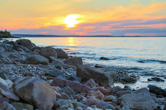 Large riverbank studded with stones. Summer evening Royalty Free Stock Image