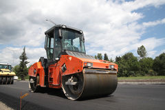 Large road-roller paving a road Stock Photography