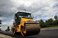 Large road-roller paving a road Royalty Free Stock Images