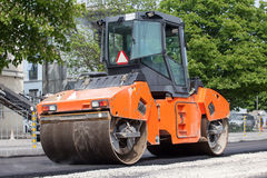 Large road-roller paving a road Stock Image