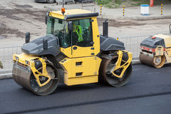 Large road-roller paving a road. Stock Images