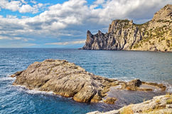 A large rock in the Bay, beautiful cloudy sky, a rocky Cape on the Black sea coast, Crimea, Novy Svet. Royalty Free Stock Photo