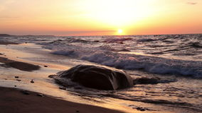 A large rock on the beach at sunset stock video