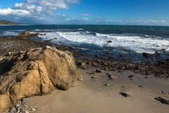 Large rock on California Beach. The rocky shore and golden sands of Leo Carillo Beach in Southern California, with mountains in the background and white clouds Stock Photography