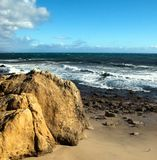 Large rock formation on California Beach. The rocky shore and golden sands of Leo Carillo Beach in Southern California, with mountains in the background and Royalty Free Stock Photo