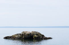 A large rock in the lake Stock Photography