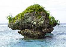 Large Rock In Ocean. A picture of a large rock in a beautiful ocean at Tanguisson Beach in Guam Stock Photography