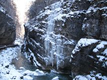 Large rock with overhanging icicles on the banks of the mountain river in winter royalty free stock photography