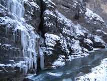 Large rock with overhanging icicles on the banks of the mountain river in winter stock photos