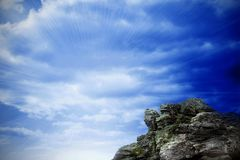 Large rock overlooking bright blue sky Stock Photos